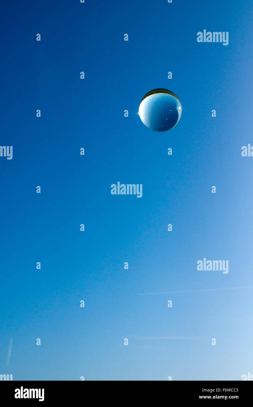single crystal ball and bubbles on blue sky - Stock Image