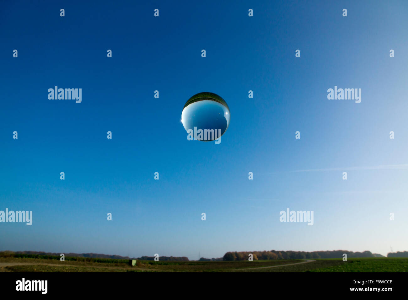 single crystal ball and bubbles in front of blue sky - Stock Image