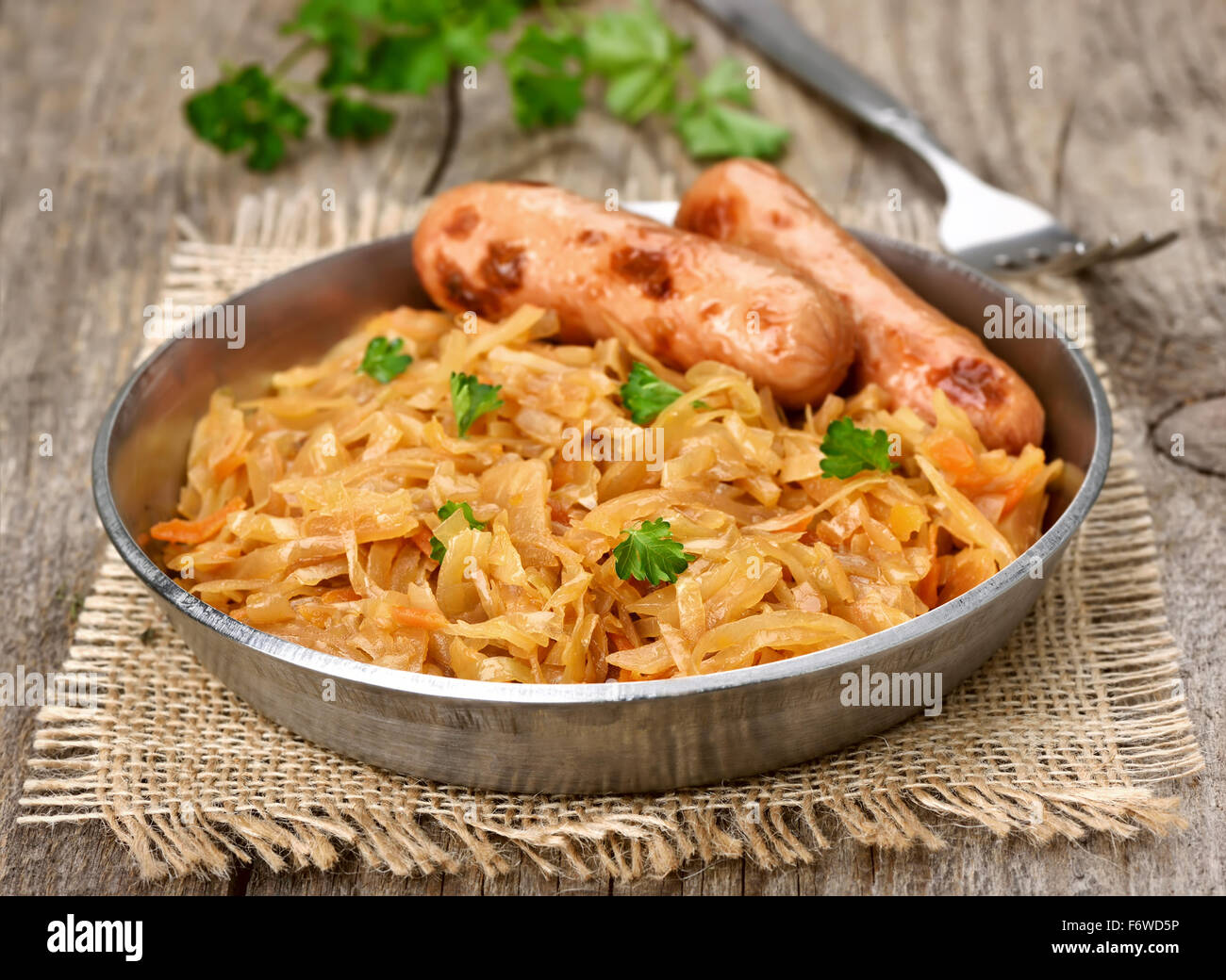 Stew cabbage with sausages in a pan Stock Photo