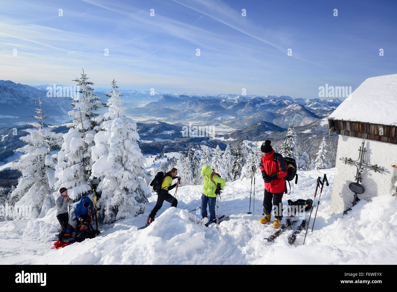 Group of persons back-country skiing standing at the summit of Spitzstein, Inn valley and Mangfall range in the - Stock Image