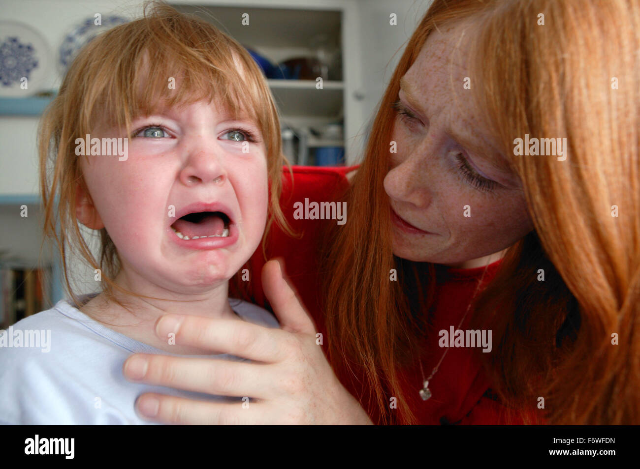 Stressed Mother with tearful young girl, - Stock Image