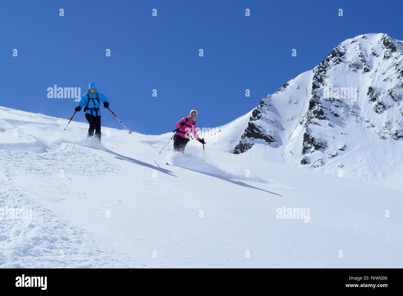 Two female backcountry skiers downhill skiing, Gleirscher Rosskogel, Pforzheim Hut, Sellrain, Stubai Alps, Tyrol, - Stock Image