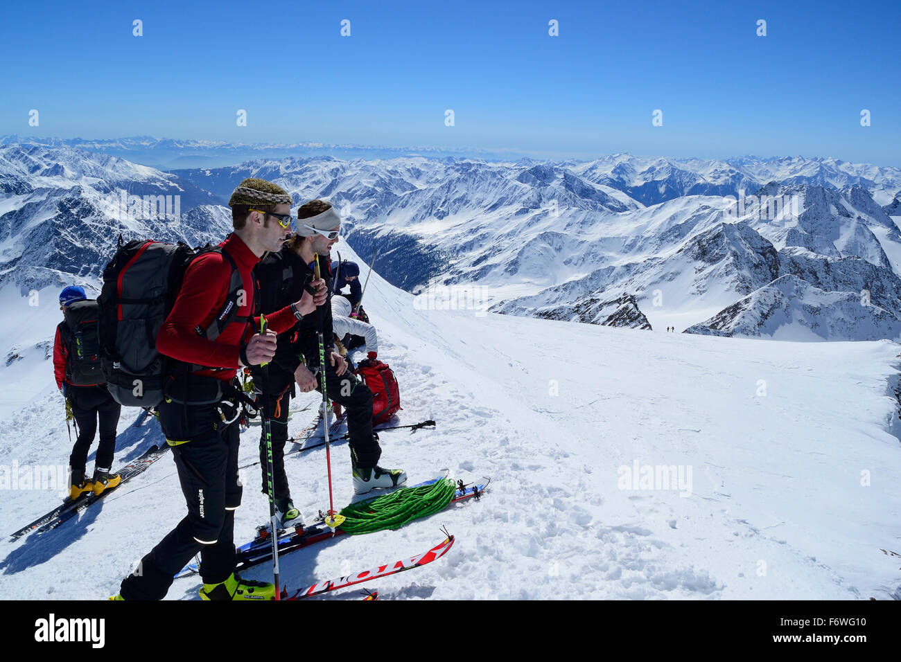 Group of persons back-country skiing standing in notch in front of Weisskugel summit, Weisskugel, Oetztal range, - Stock Image