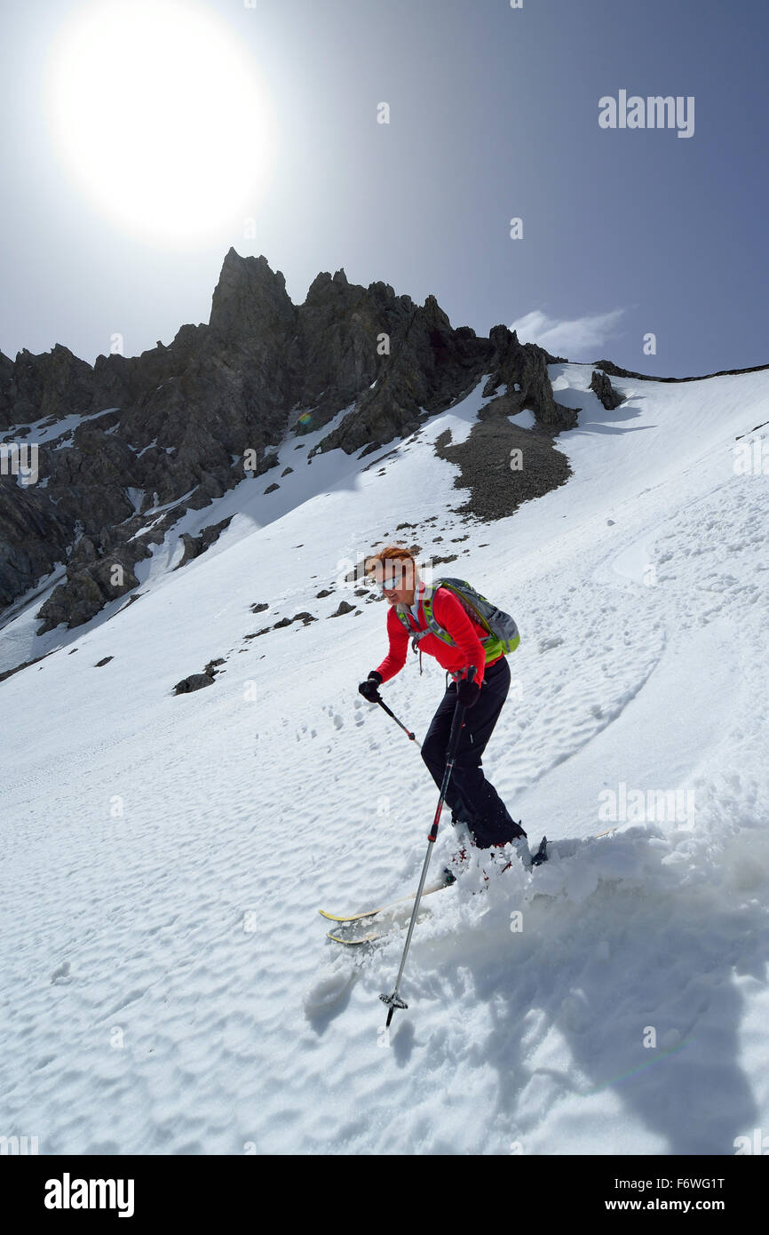 Female backcountry skier downhill skiing through Loferer Seilergraben, Berchtesgaden Alps, Berchtesgaden National - Stock Image