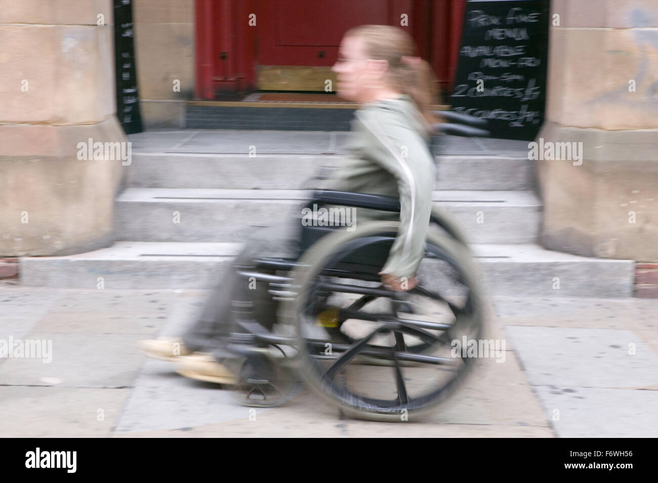 Young wheelchair user moving past a flight of steps which she is unable to access, - Stock Image