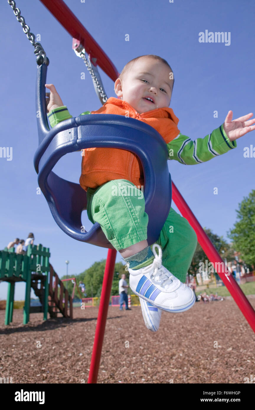 Baby boy swinging in an infant's swing at the playground, - Stock Image