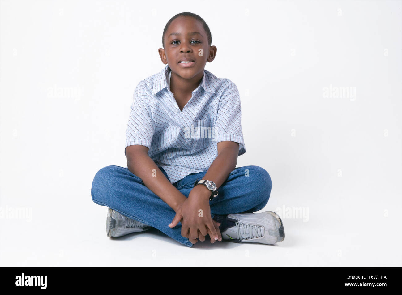 Young boy sitting on the floor crossed legged, - Stock Image