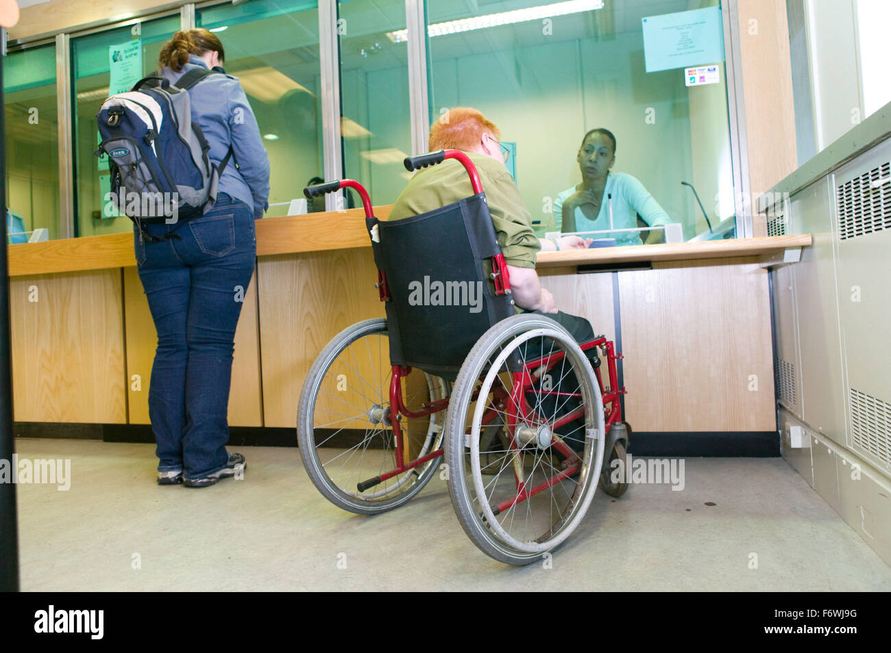 Man who is a wheelchair user paying his council tax bill at an accessible low level desk, - Stock Image