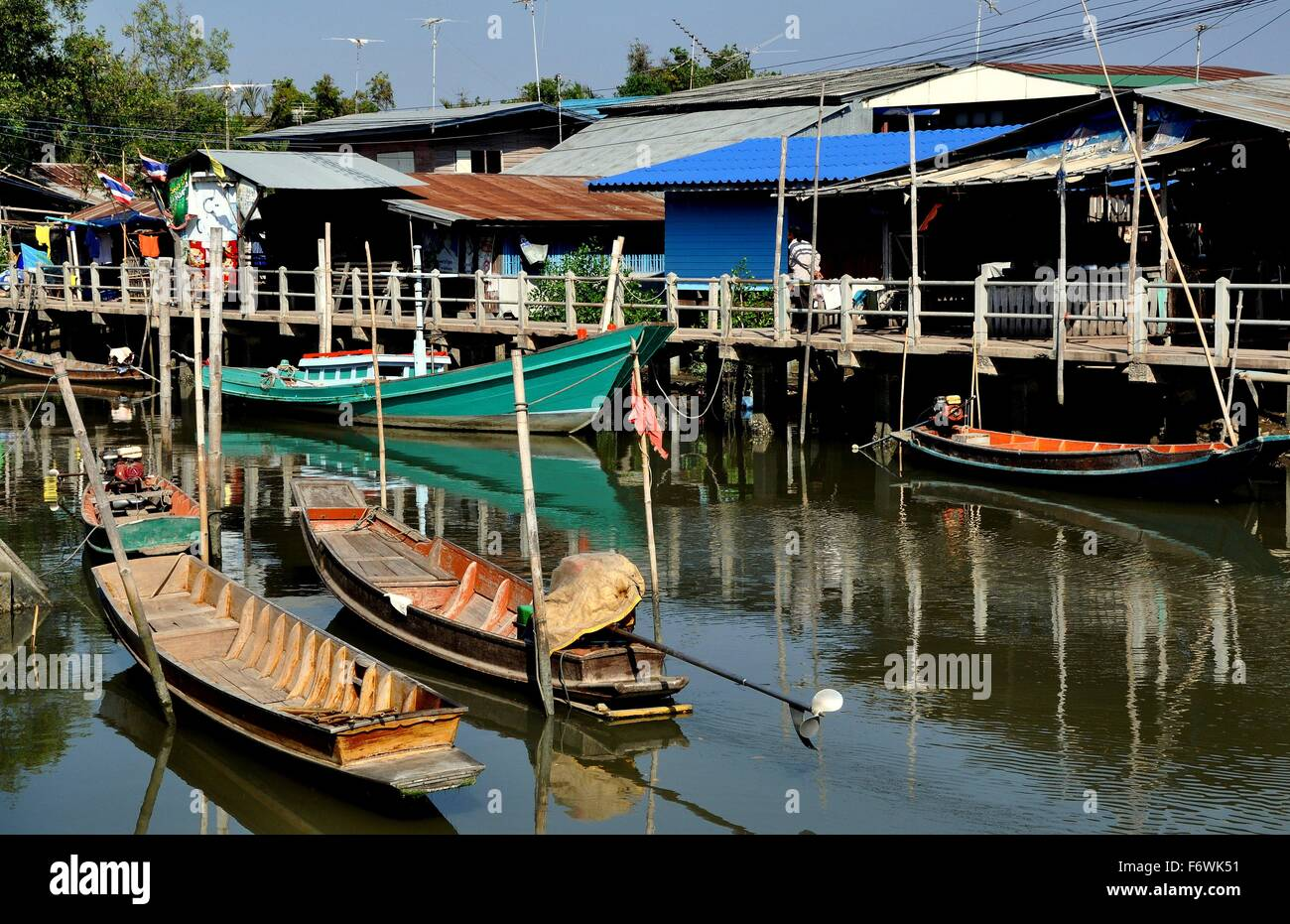 Samut Songkhram:   Old wooden fishing boats docked in front of a cluster of Thai houses at a small fishing village - Stock Image