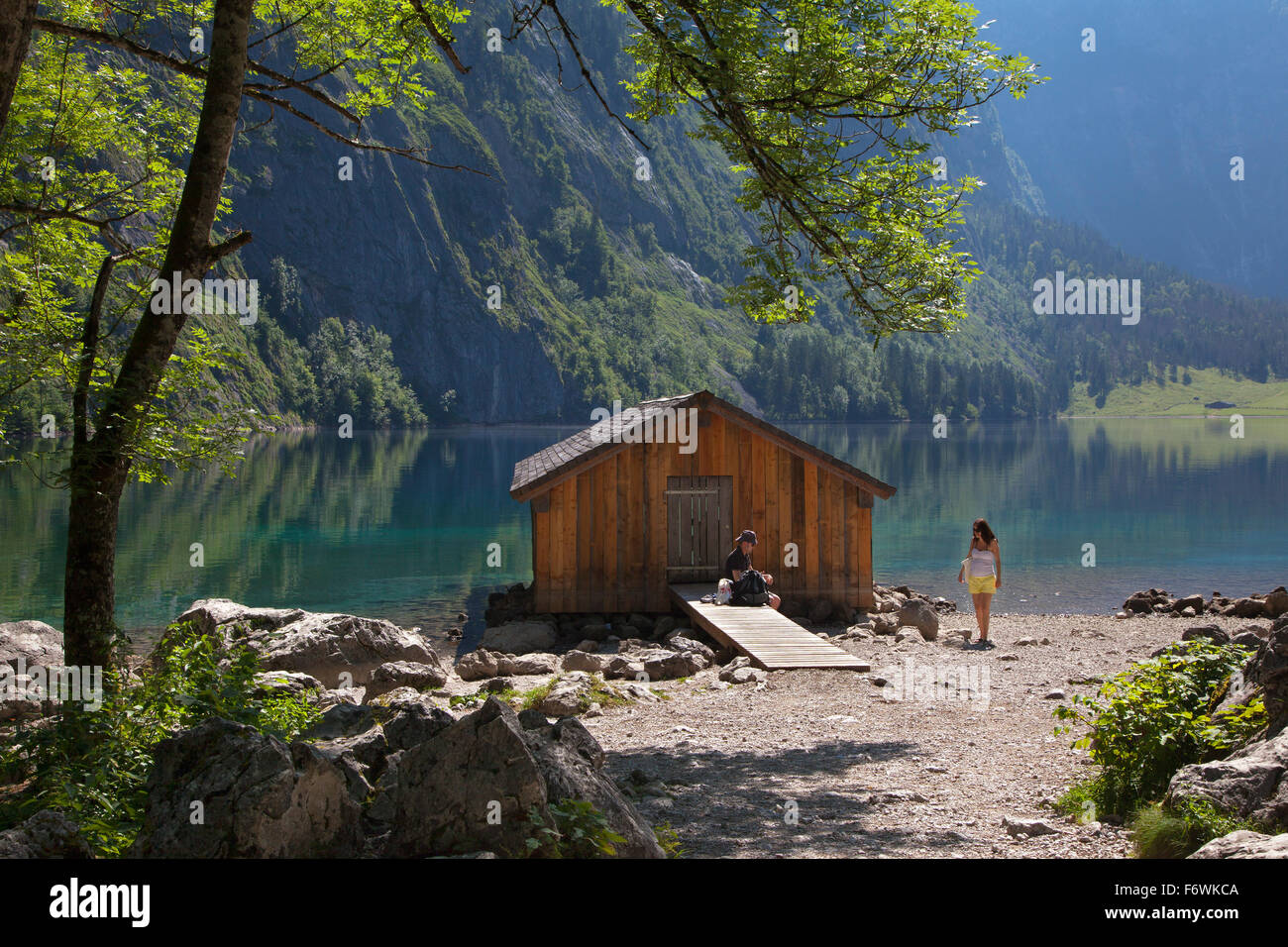 Young couple having a rest at a boat house at Obersee, Koenigssee, Berchtesgaden region, Berchtesgaden National Stock Photo