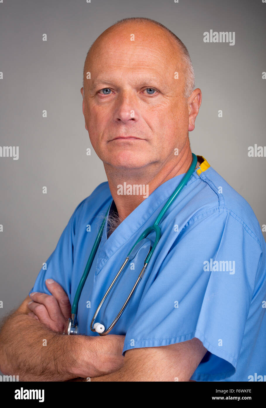 Doctor in blue scrubs, with arms folded and a stethoscope around his neck, against a grey background. - Stock Image
