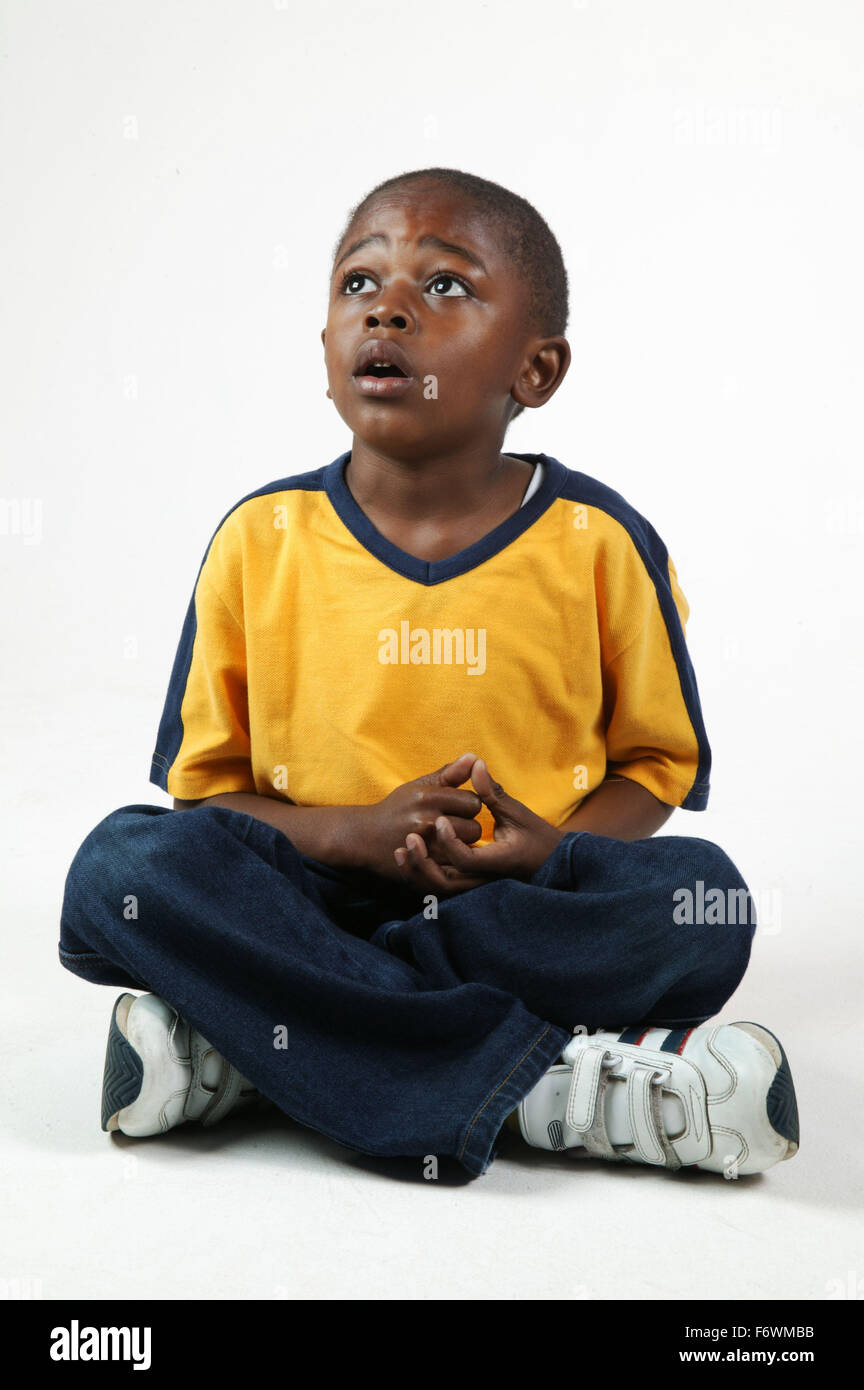 Young black boy sitting with crossed legs, - Stock Image