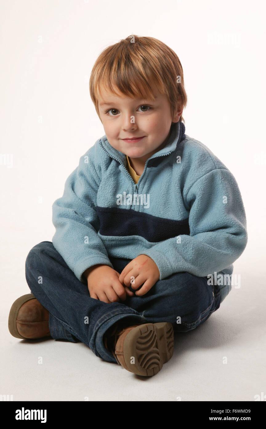 Young boy sitting crossed legged, - Stock Image
