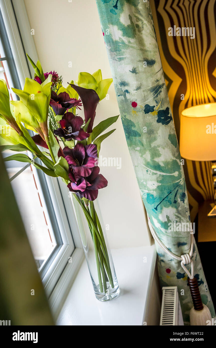Vase of flowers on a windowsill in a contemporary house. - Stock Image