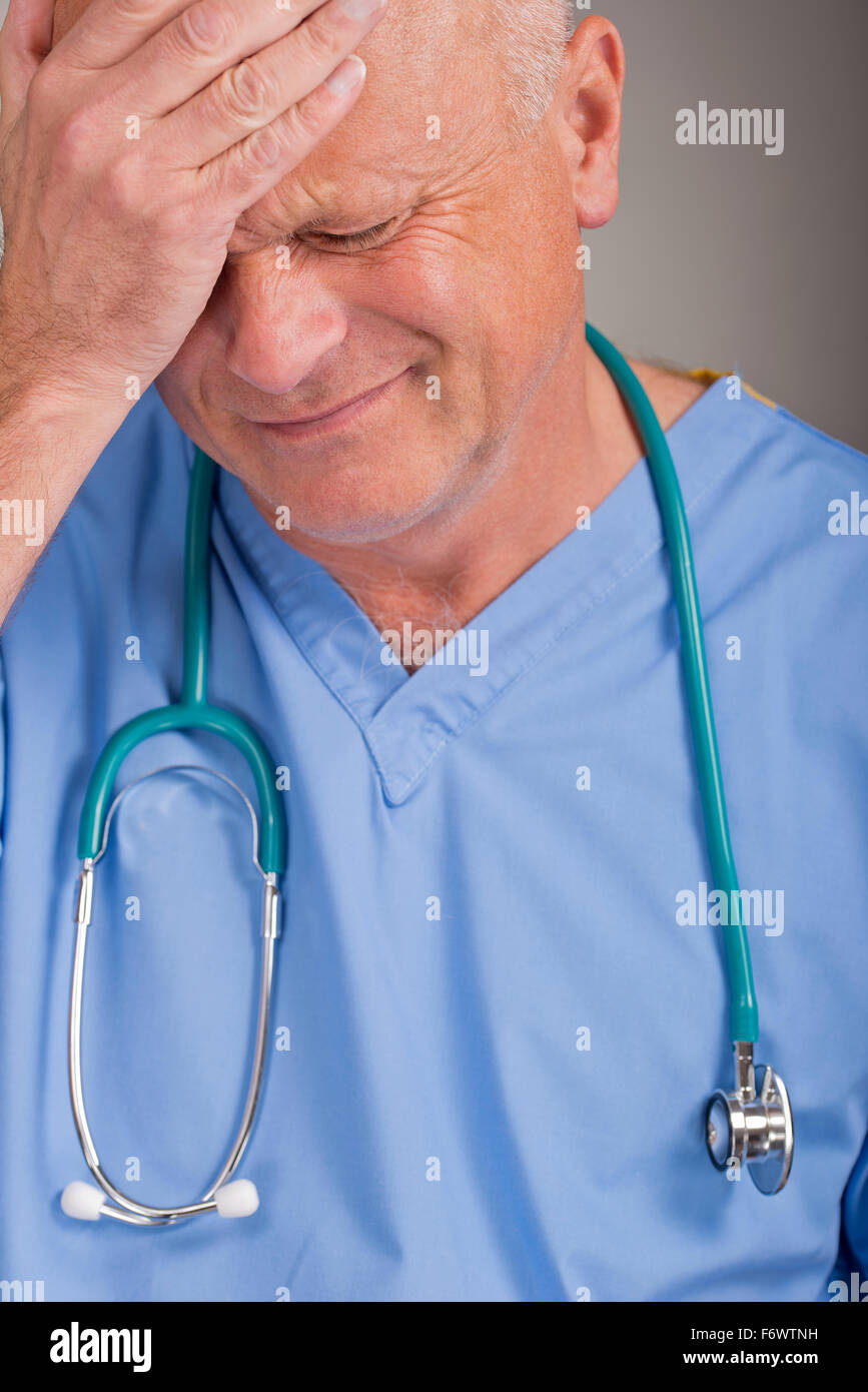 Distraught doctor wearing blue scrubs, with his hand on his head/face. - Stock Image