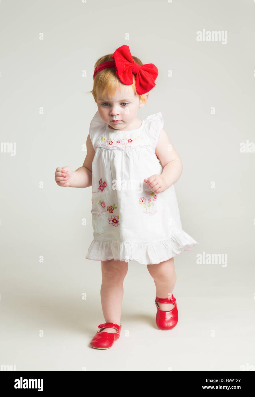 A cute little one year old girl learning to walk in red shoes and bow - 13c0384b26