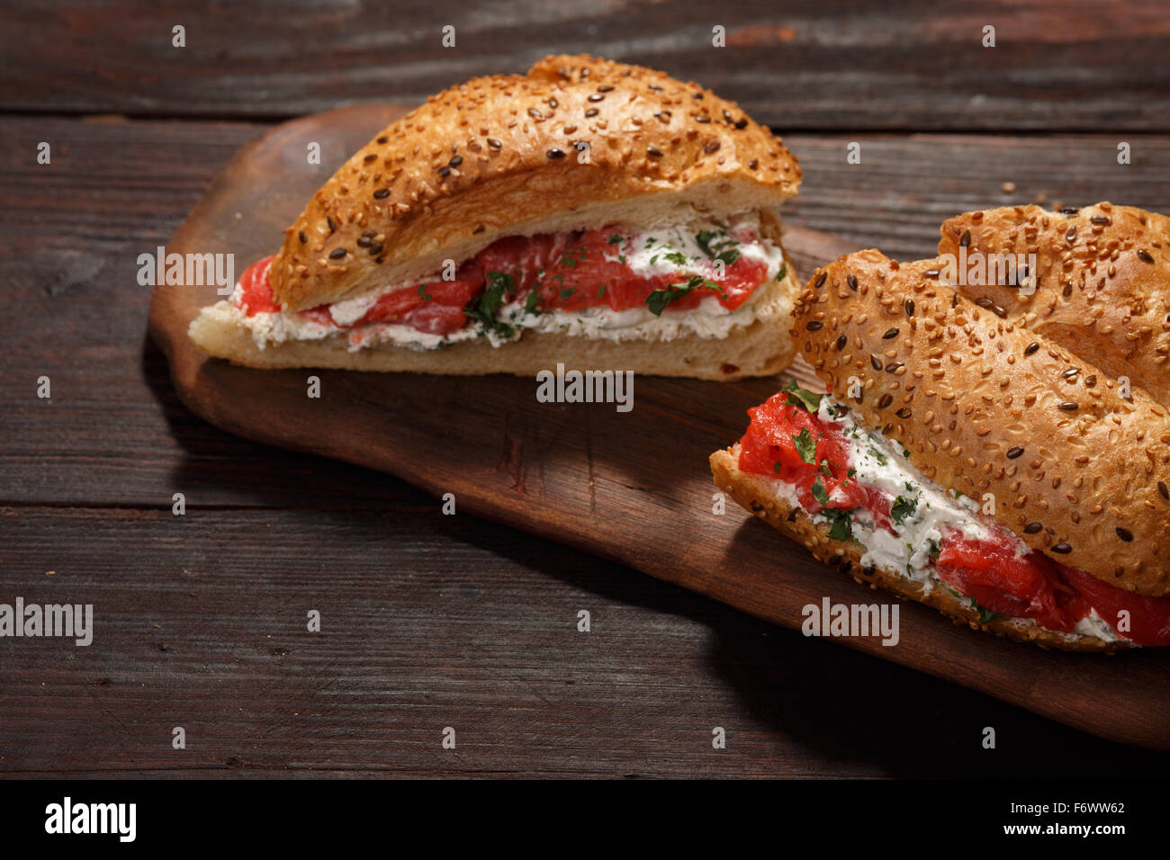 Sandwich from wholegrain bread with salmon, mild creamy cheese and herbs - Stock Image