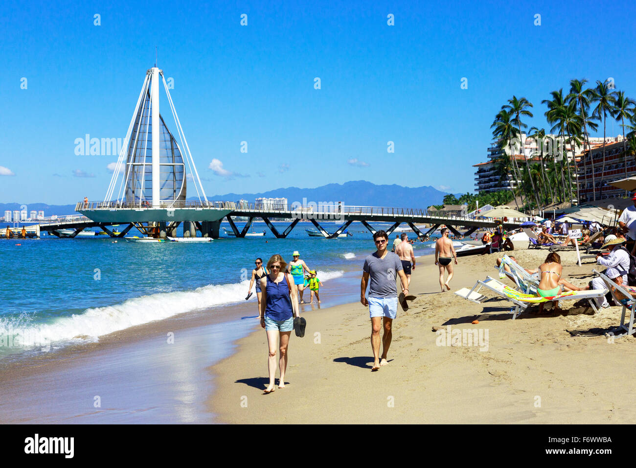 Beach at Zona Romantica, old town of Puerto Vallarta, Mexico with the Los Muertos Pier in the background - Stock Image