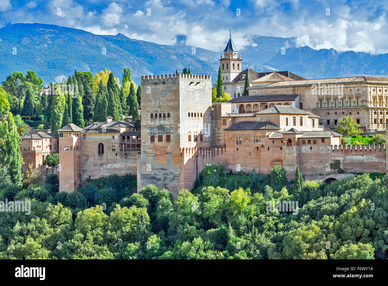 GRANADA ANDALUCIA SPAIN THE ALHAMBRA WITH STORM CLOUDS OVER THE SIERRA NEVADA AND AUTUMNAL TREES - Stock Image