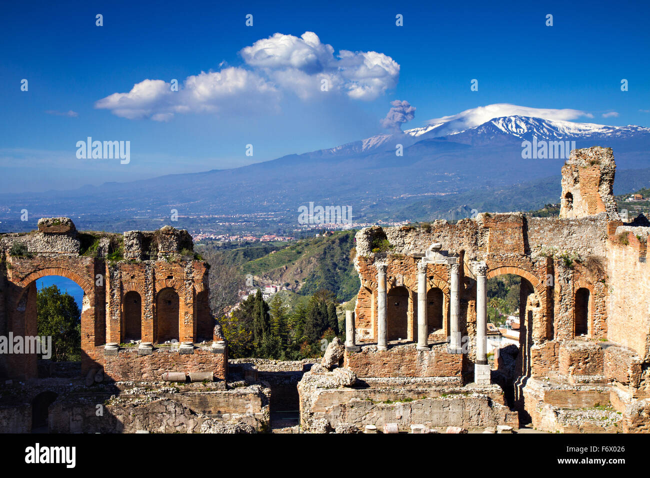 Ruins of the Greek Roman Theater with Etna erupting, Taormina, Sicily, Italy - Stock Image