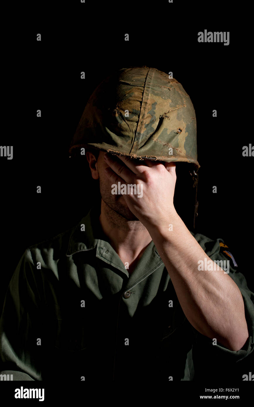 American GI from the Vietnam War, covering his face with his hand.despair,abuse,bullying,victim,scared,worries,crying,tearful,sa - Stock Image