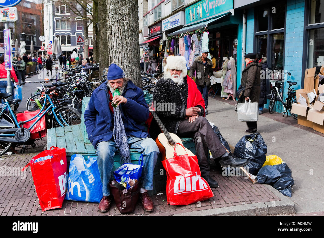 two Tramps sitting on a bench in a Amsterdam street - Stock Image
