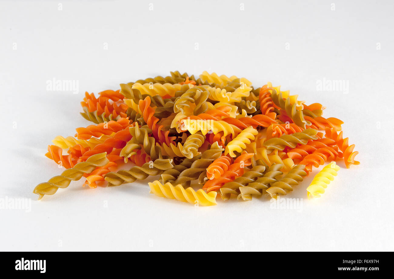 Uncooked coloured Rotini Pasta against a white background - Stock Image