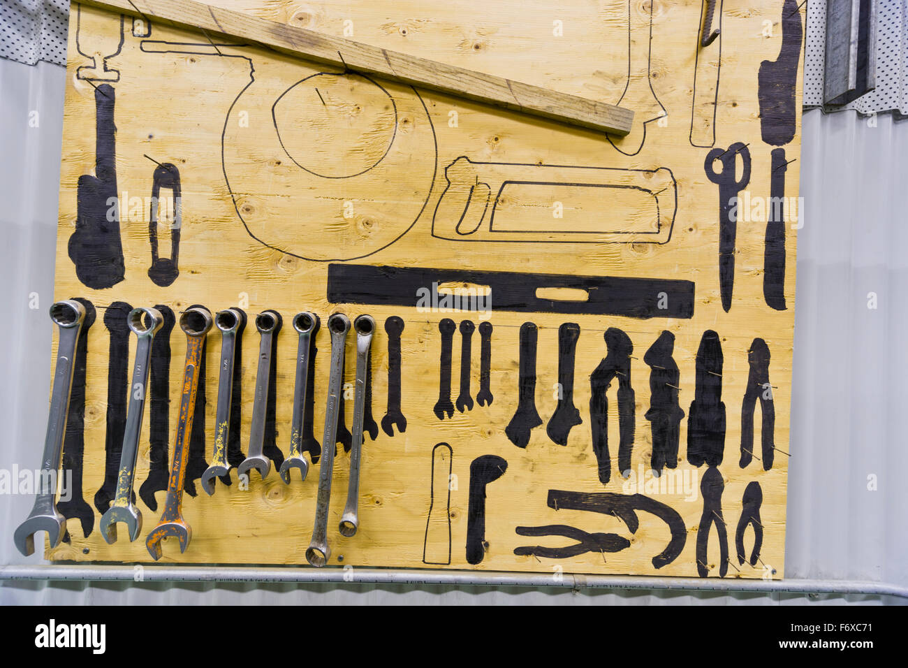Tools and their outlines hang on a wall inside an electrical power ...