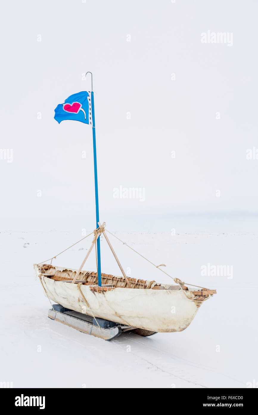 A White Umiak Skin Boat Sits On Skids The Sea Ice With Flag Flying
