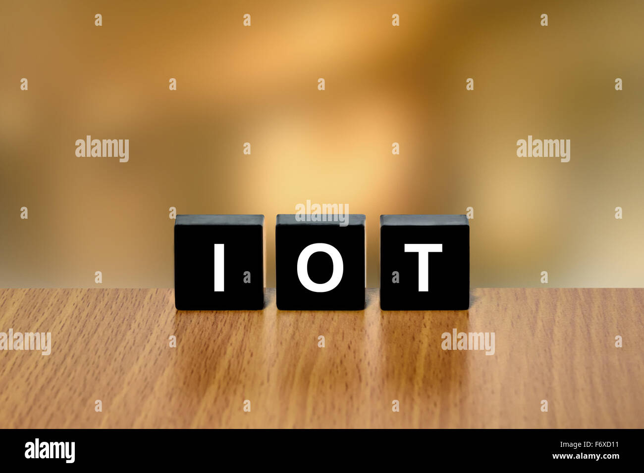 IOT or Internet of Things on black block with blurred background - Stock Image