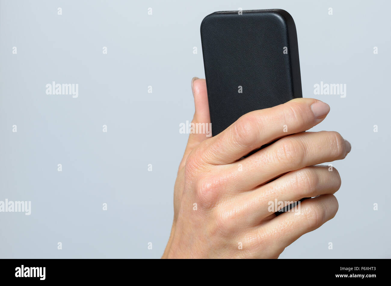 Hand holding a black cellular Against Gray Background with Copy Space. Stock Photo