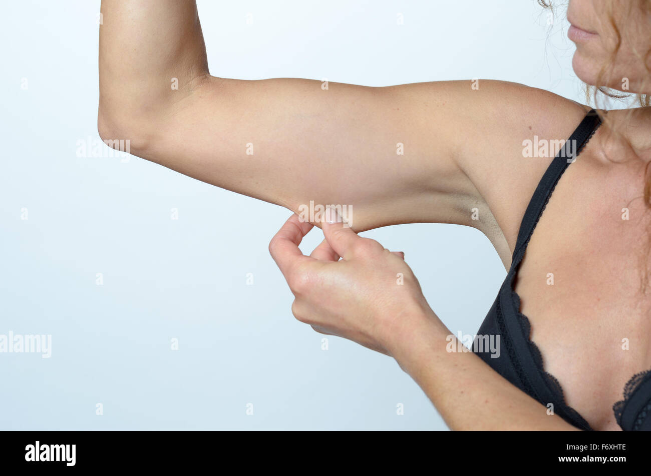 Middle aged woman displaying the loose skin or flab due to ageing on her upper arm pinching it between her fingers, - Stock Image