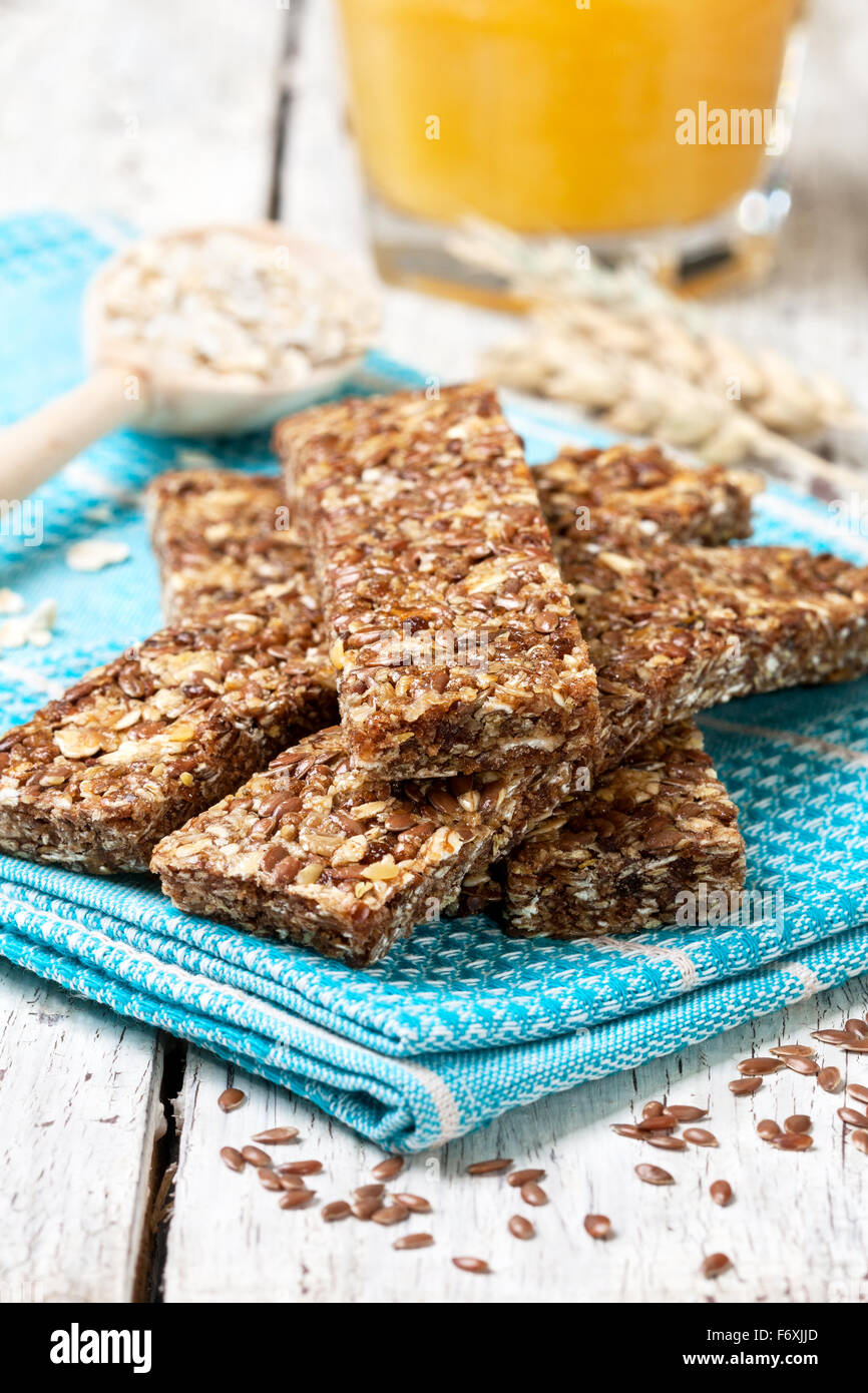 cereal bars, oatmeal, flax seeds and orange juice on a wooden background - Stock Image