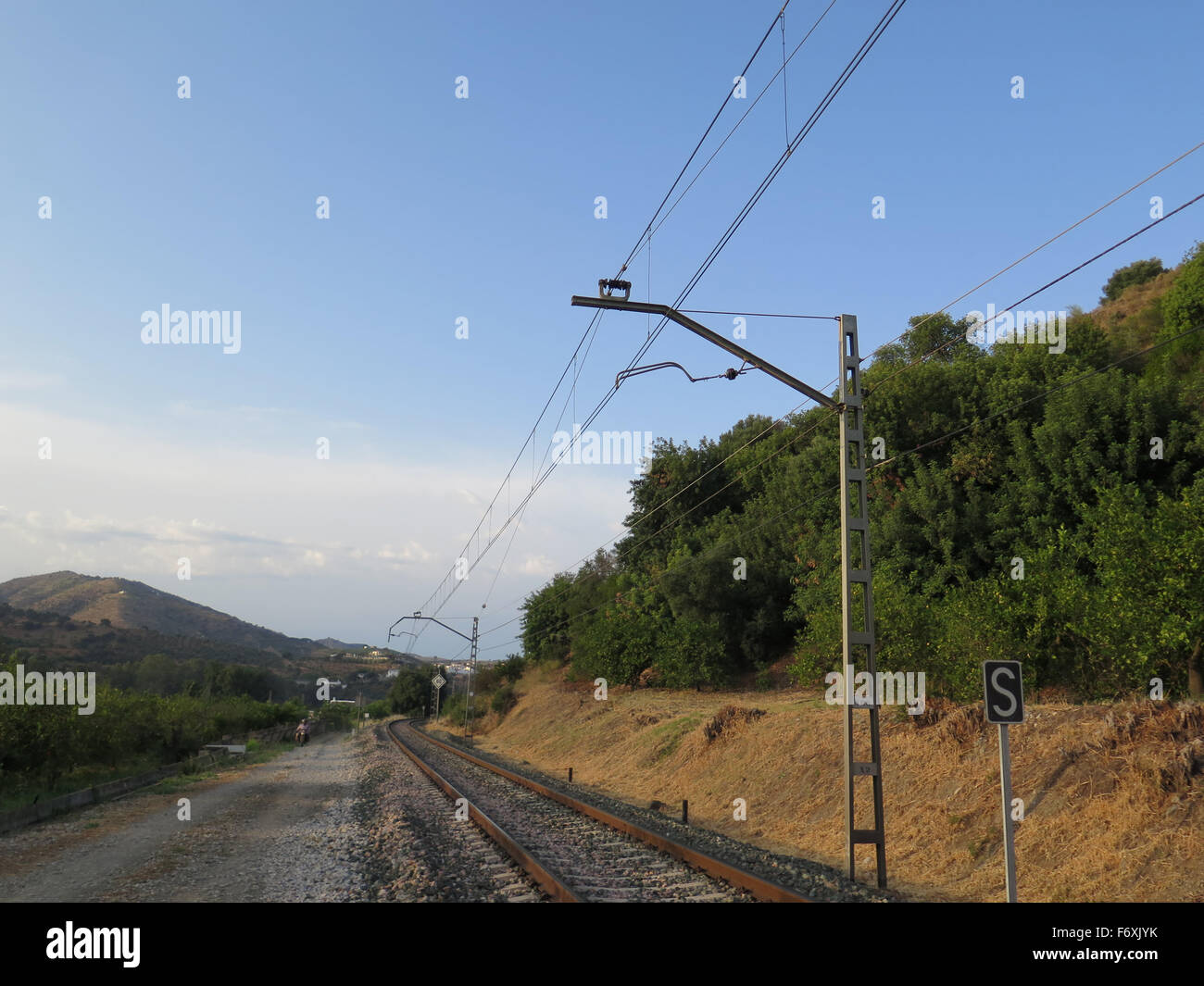 Railway track and country road on sunny day near Alora, Andalusia - Stock Image