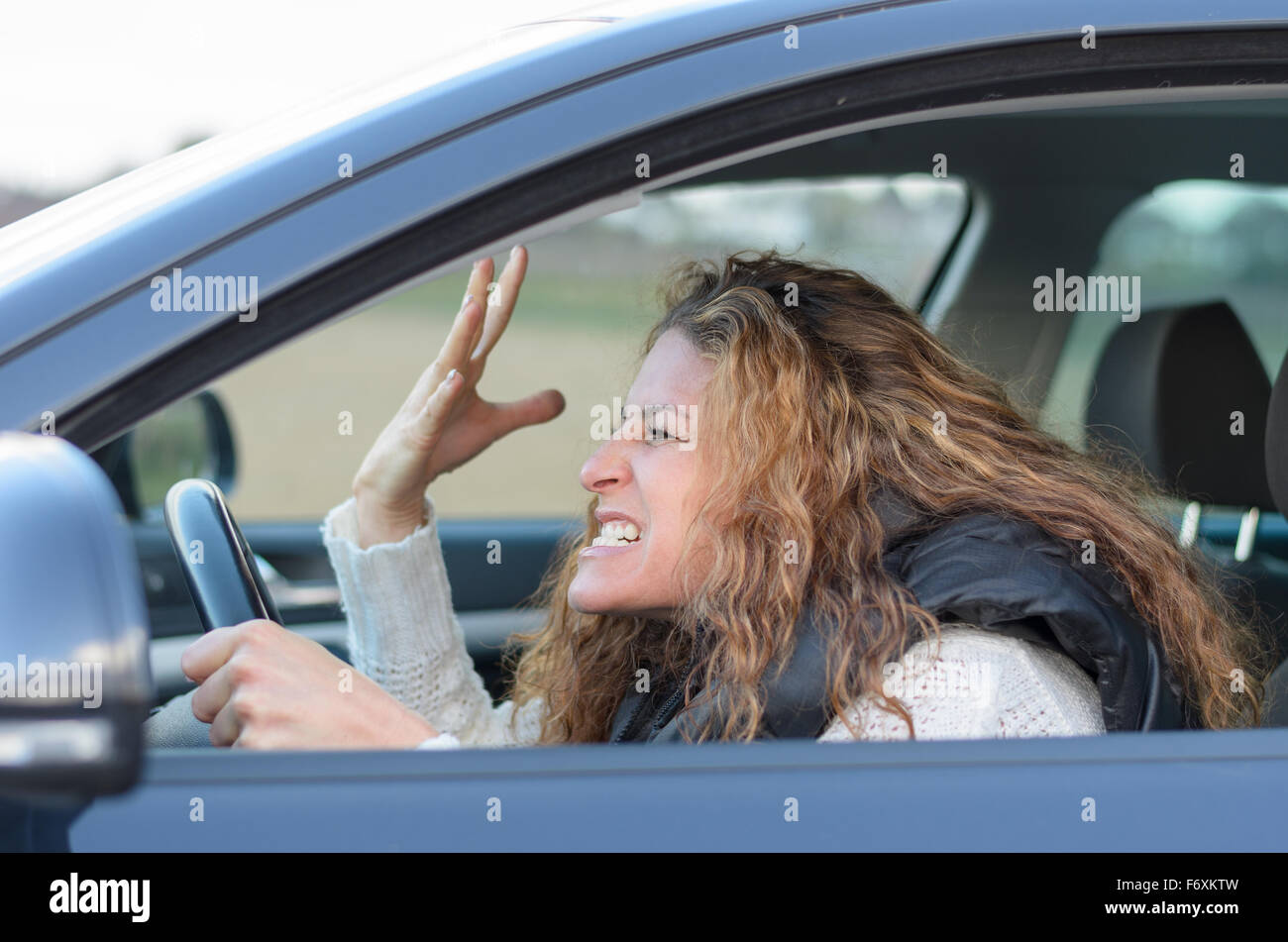 woman ist driving her car very aggressive and gives gesture with his fist - Stock Image