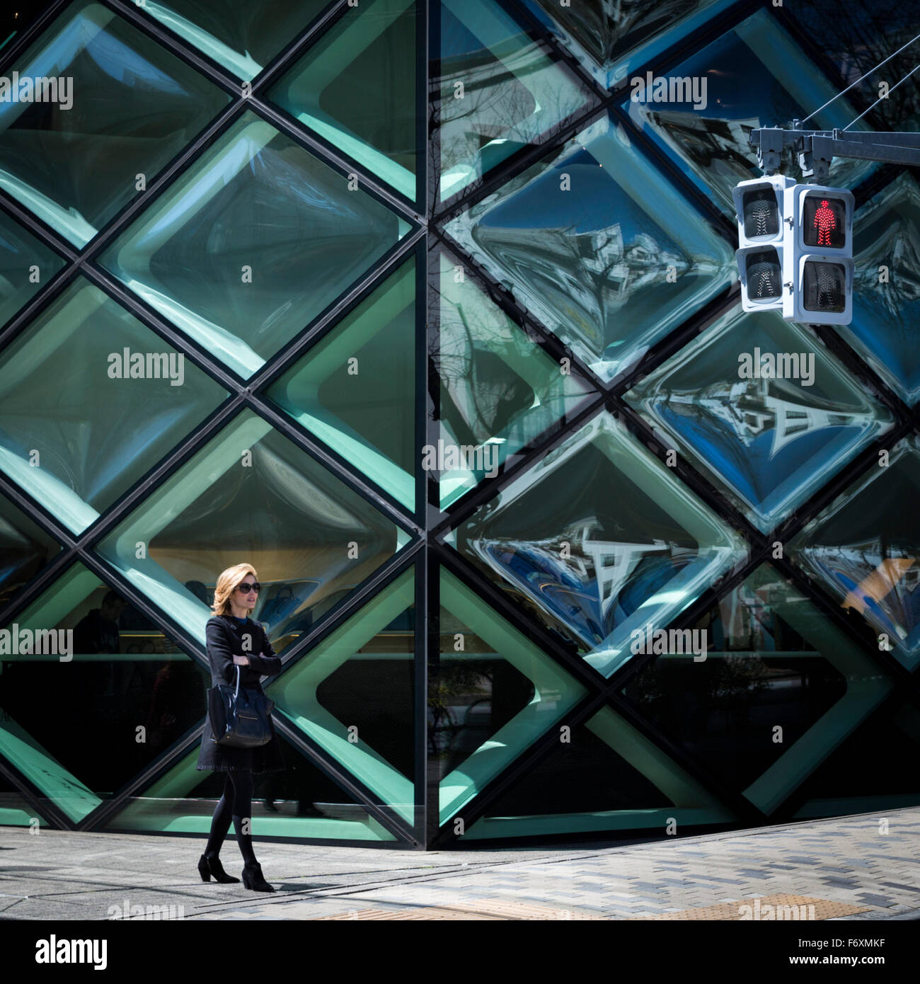 Fashionable woman outside the geometric glass panes of the Prada store in the trendy Aoyama district of Tokyo Stock Photo