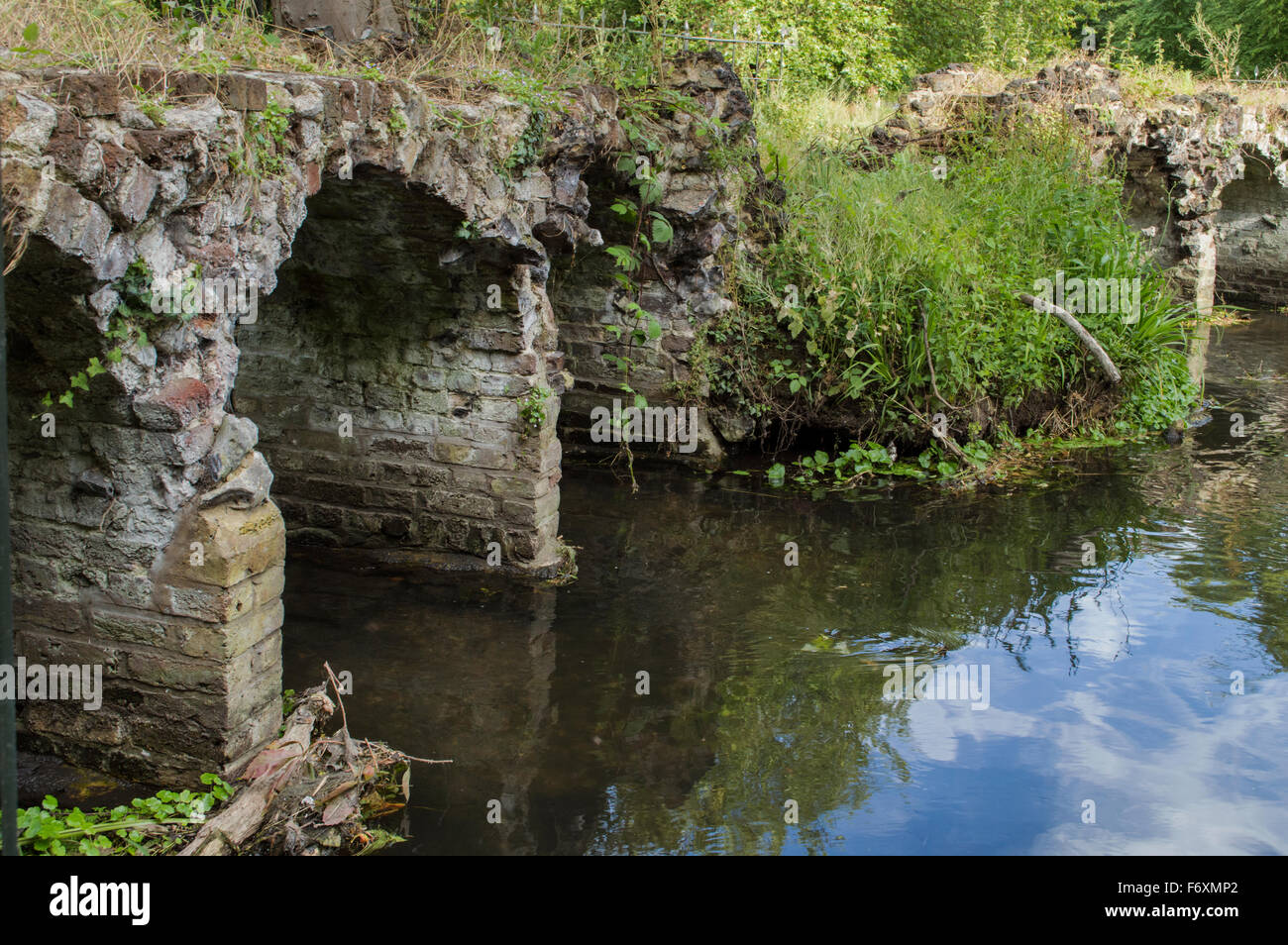 A side angle of an old stone bridge sitting in a river surrounded by greenery - Stock Image