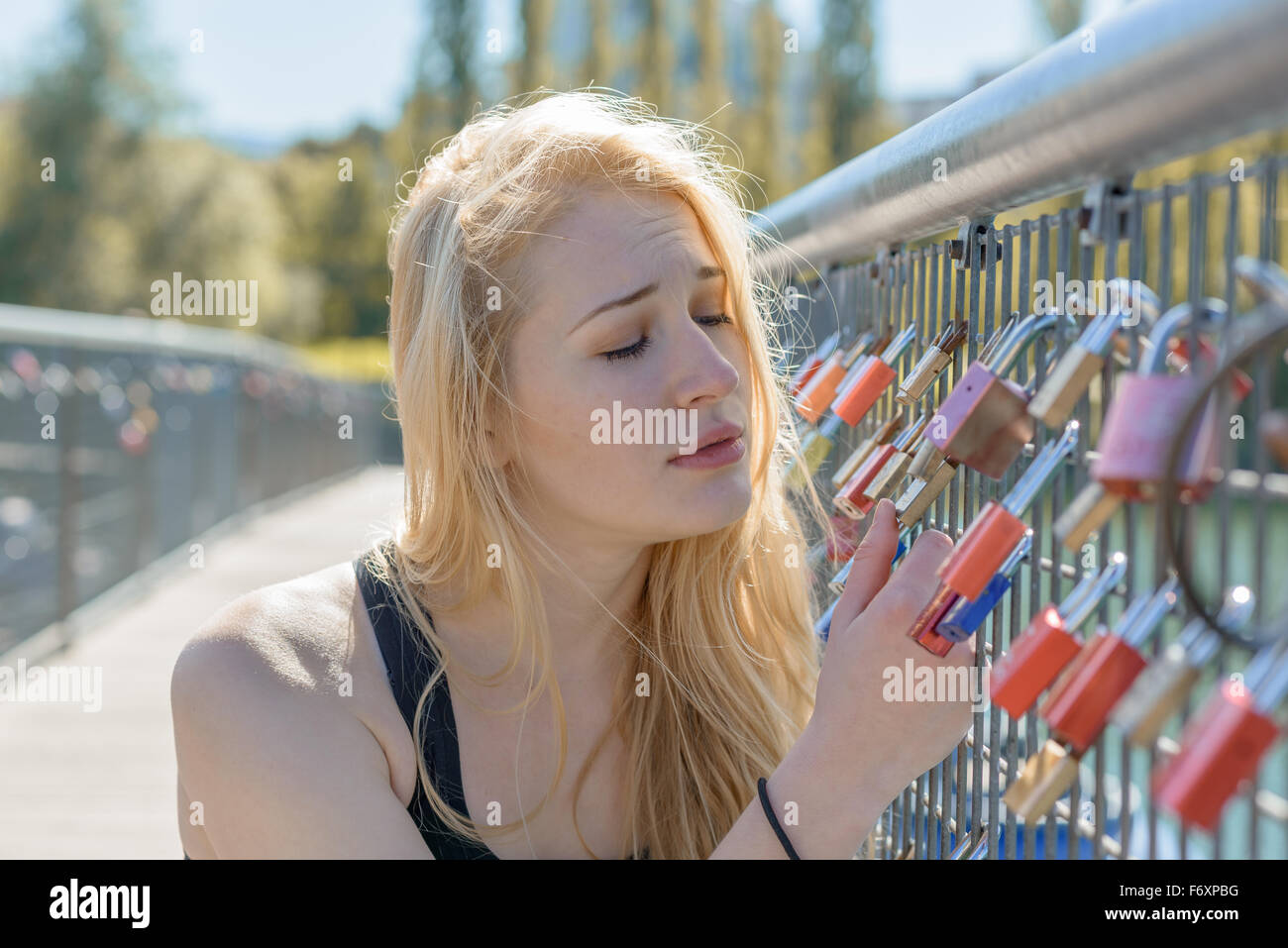 Beautiful young blond woman holding padlocks as a sign for endless love with a sad facial expression - Stock Image