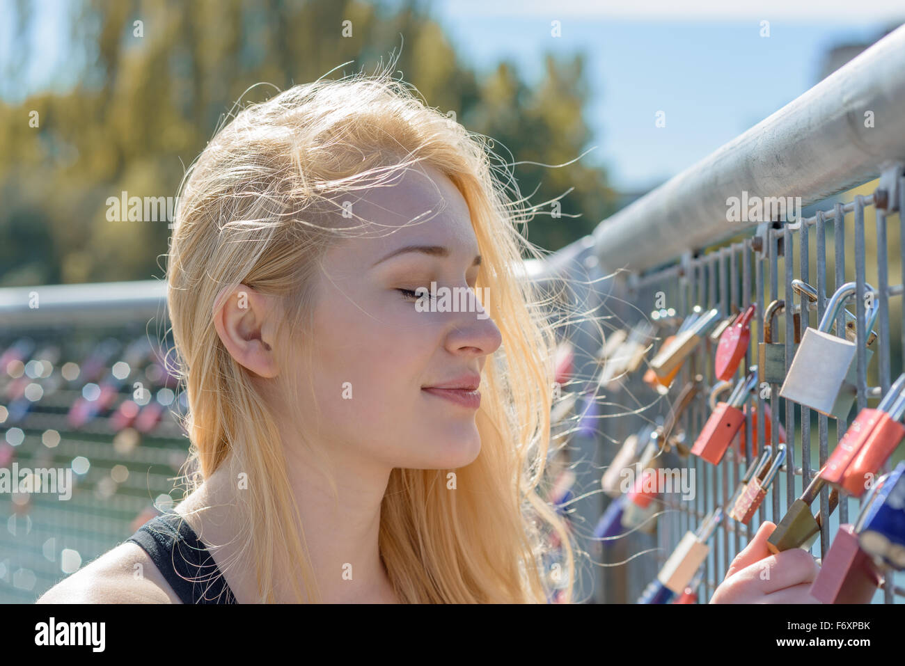 Beautiful young blond woman holding padlocks as a sign for endless love - Stock Image