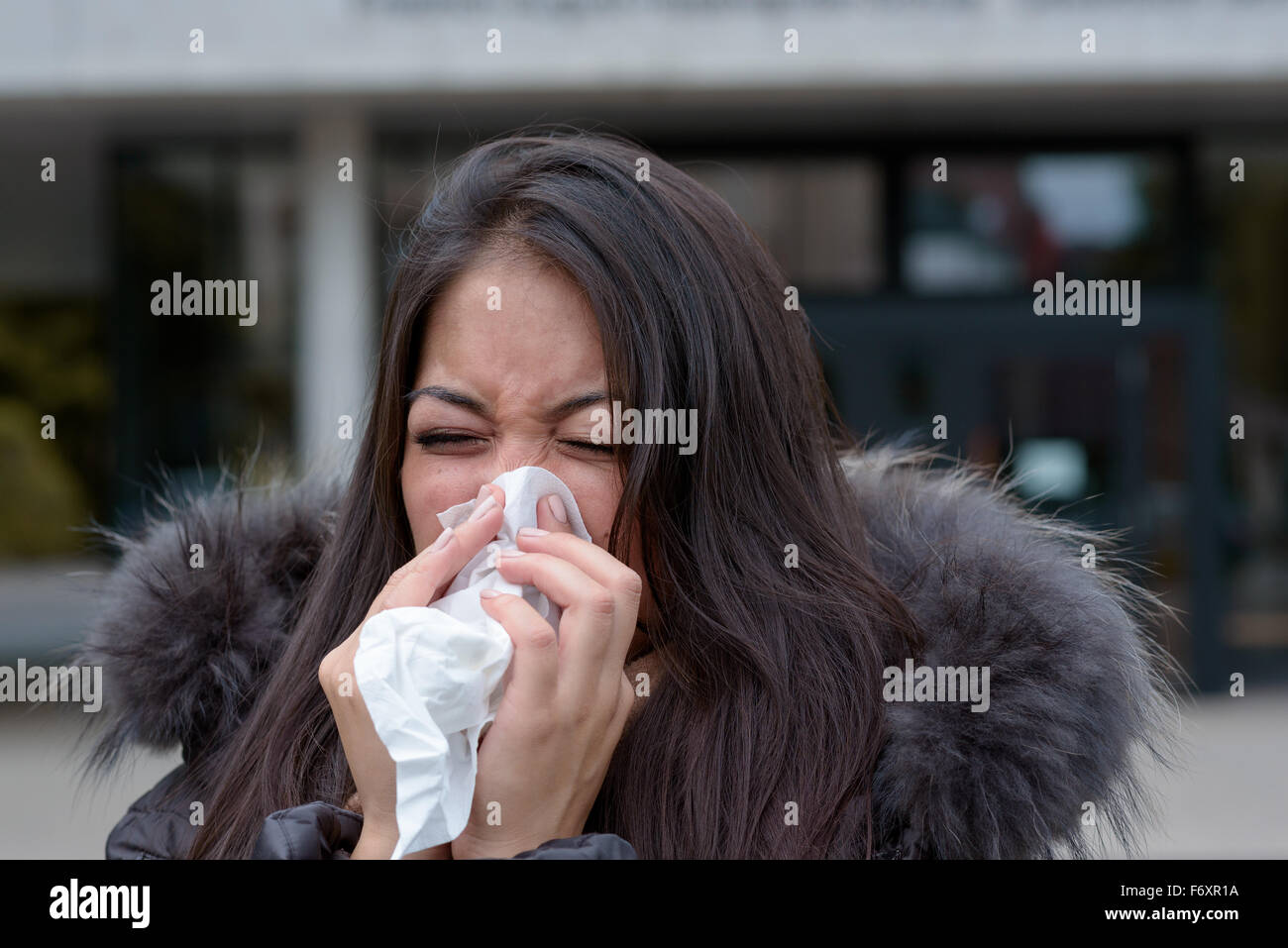 Woman with a seasonal winter cold and flu standing outdoors on an urban street in a furry jacket blowing her nose - Stock Image