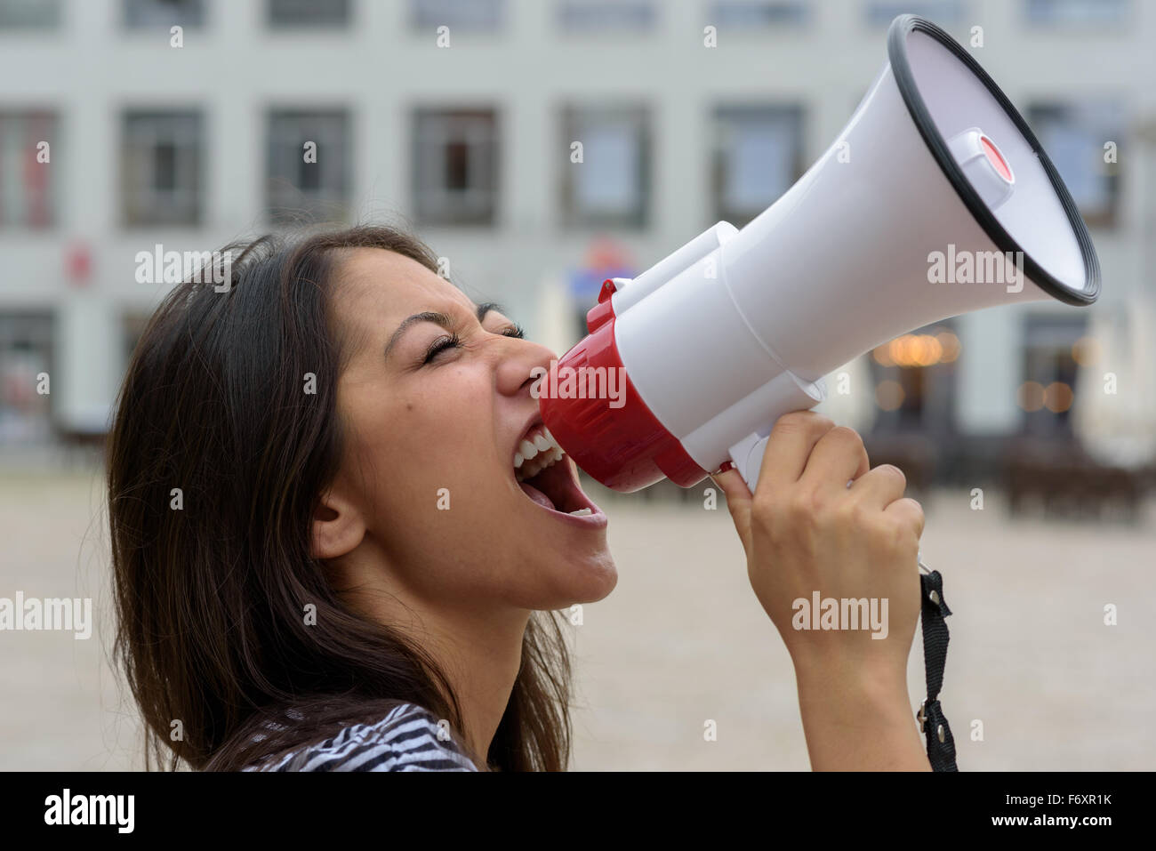 Woman yelling into a bullhorn on an urban street voicing her displaeasure during a protest or demonstration, close - Stock Image