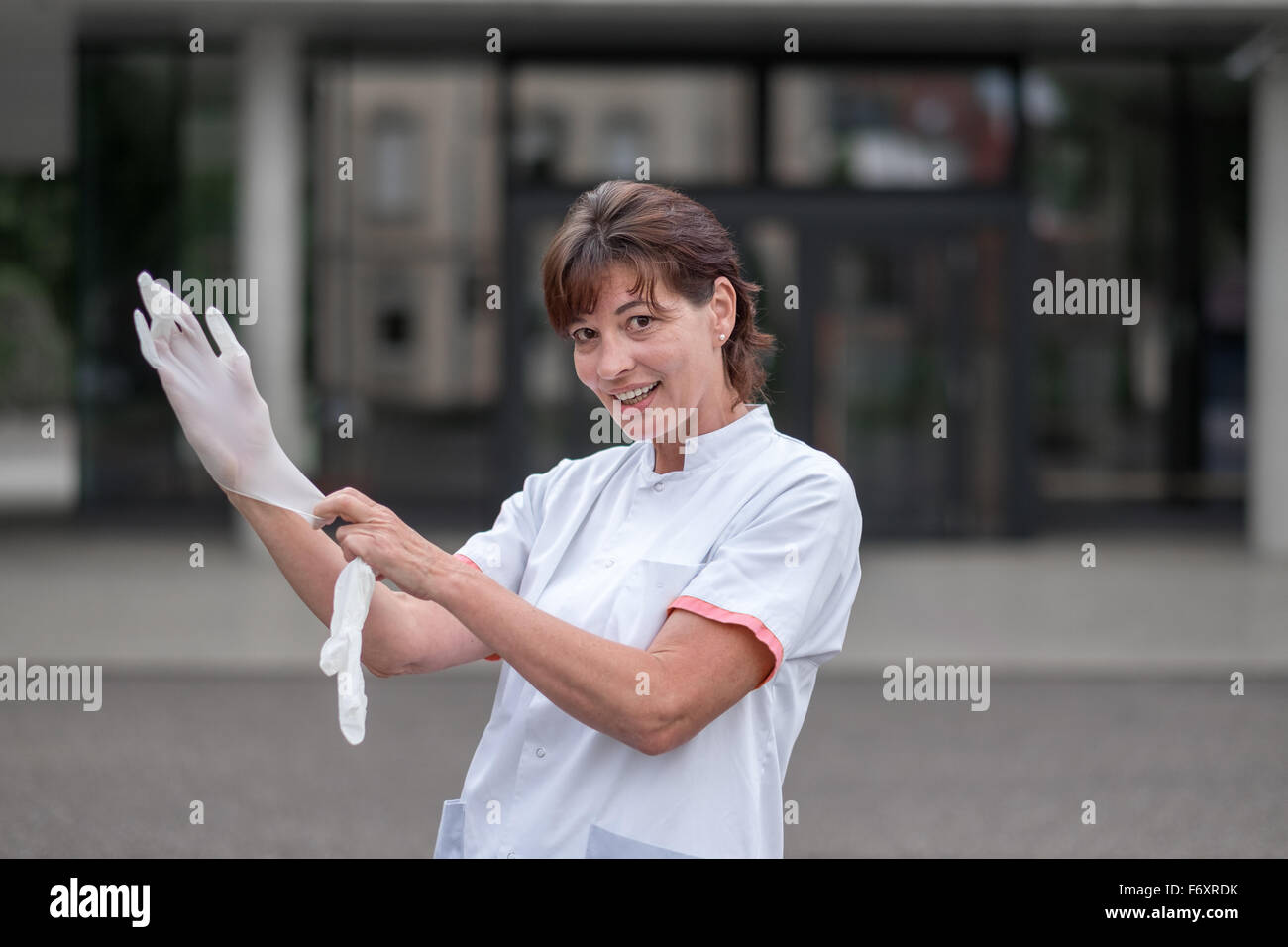 Female doctor or nurse standing outdoors in front of a hospital putting on latex gloves for protection or sterility - Stock Image