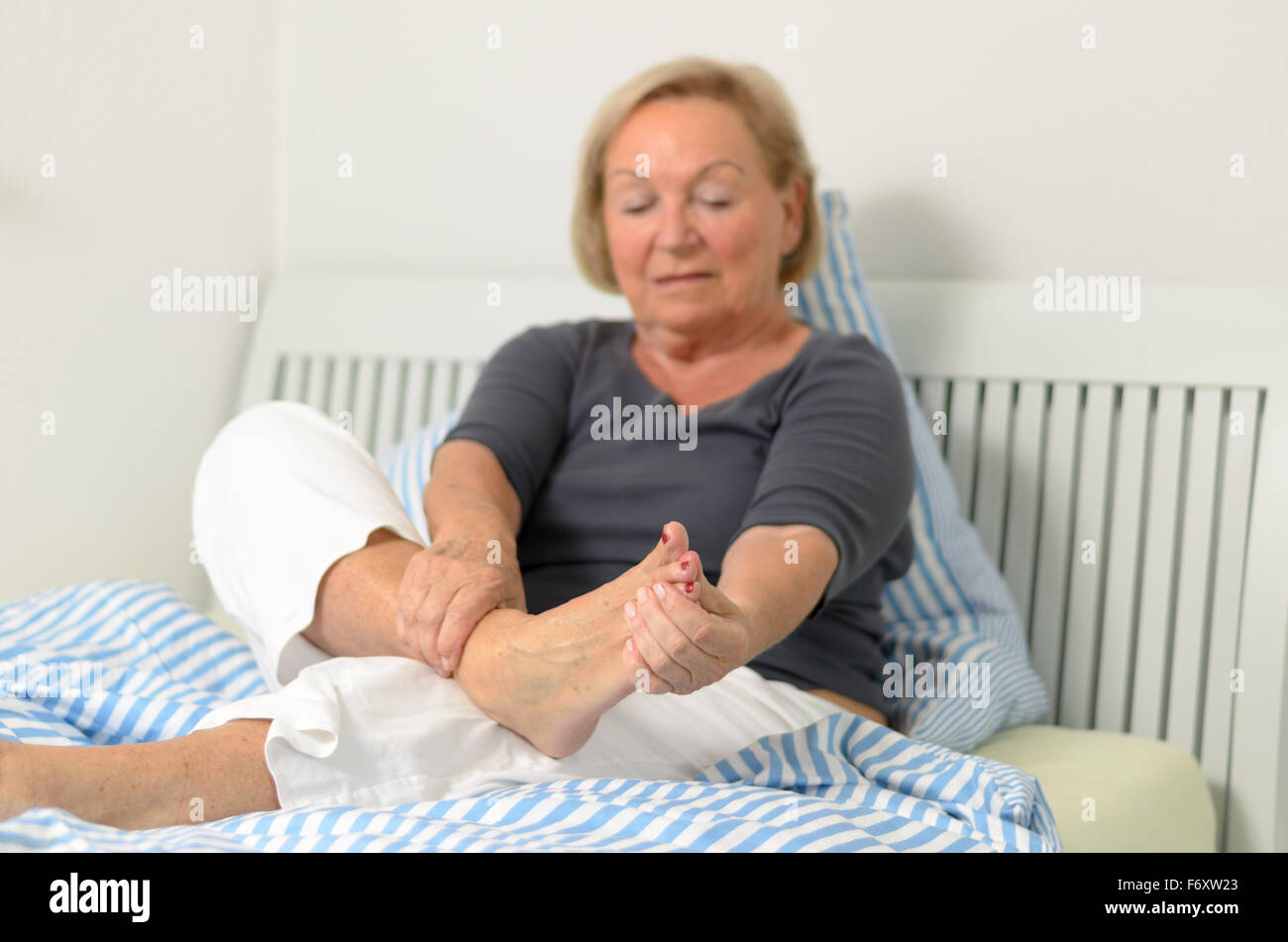 Senior lady massaging her bare foot to relive aches and pains as she sits relaxing against the pillows on her bed - Stock Image