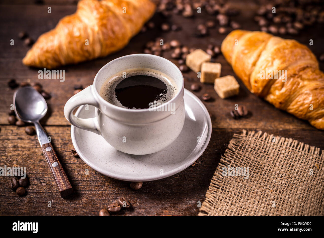 Coffee and croissant on wooden background - Stock Image