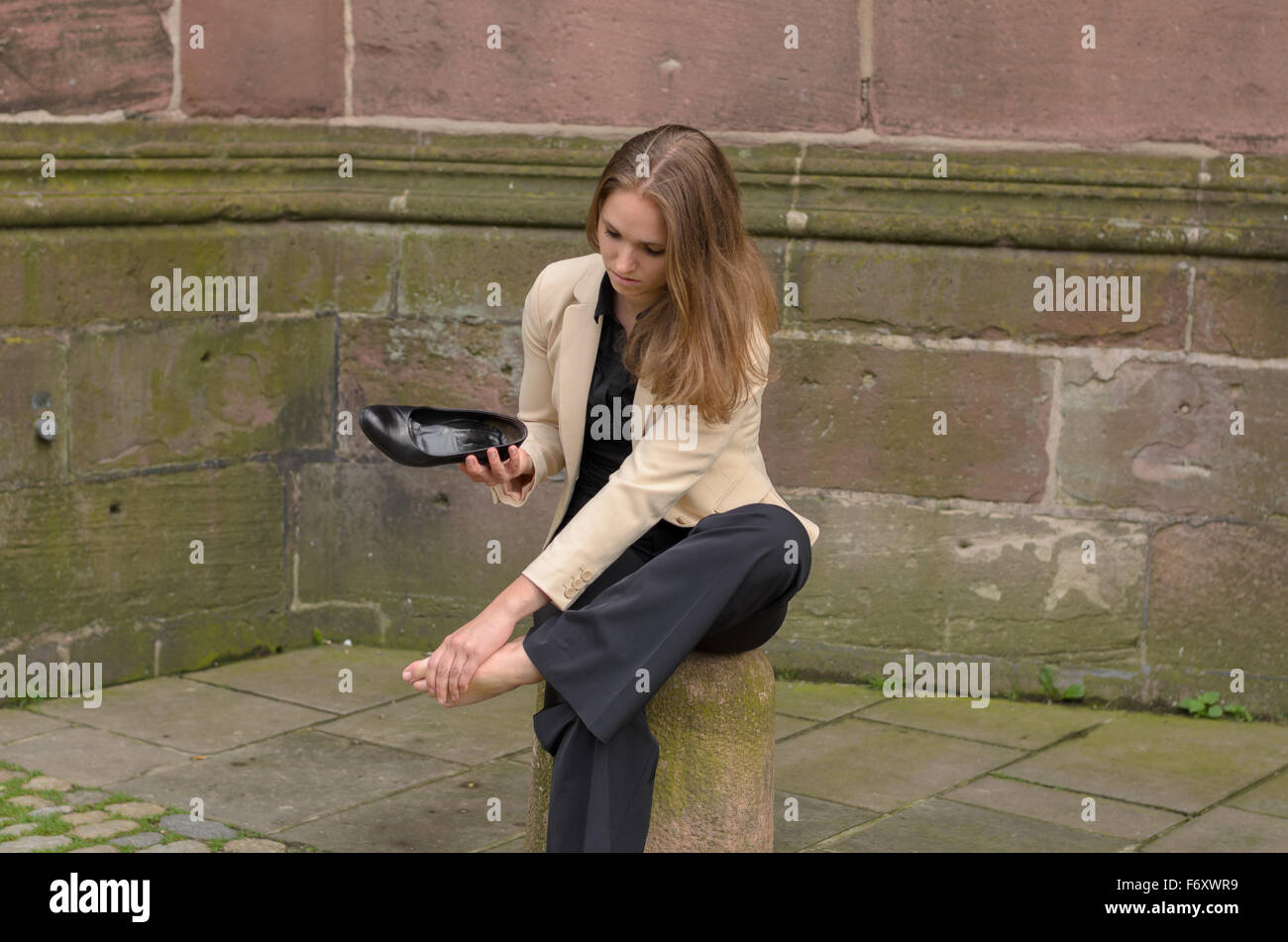 Stylish young woman with aching feet pausing in town to sit on a cement bollard as she removes her high heels to - Stock Image