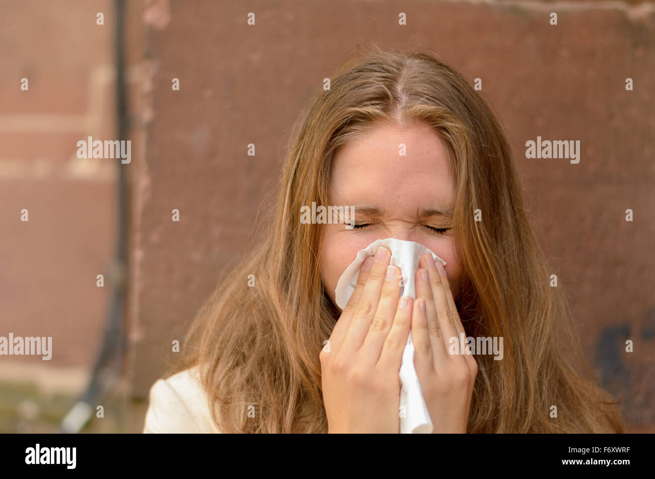 Young woman blowing her nose on a handkerchief conceptual of an illness, flu, cold, allergic rhinitis or hay fever - Stock Image
