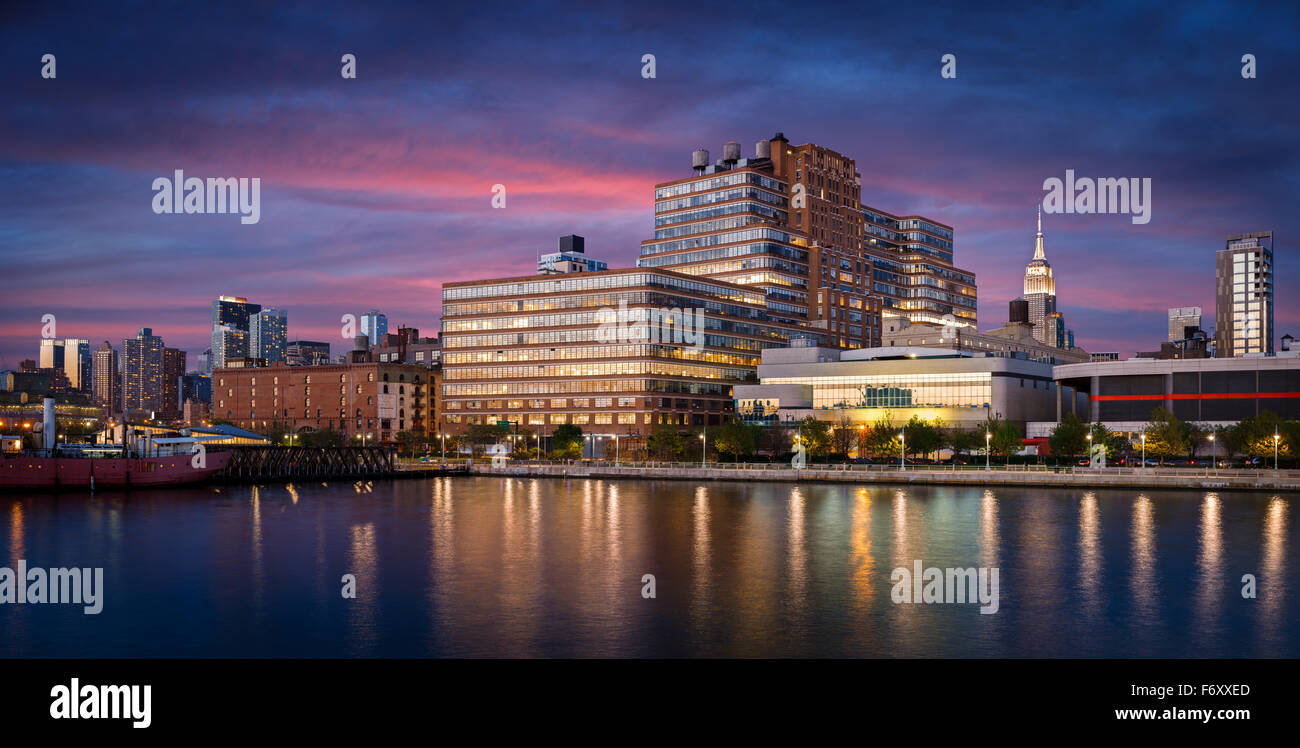 Early evening view and city lights of West Chelsea and Midtown Manhattan skyline from Hudson River. New York City - Stock Image