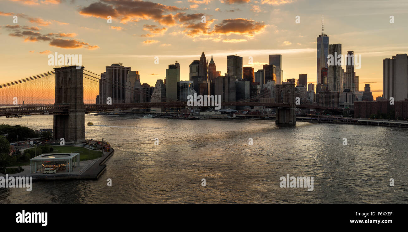 Lower Manhattan skyscrapers and Financial District skyline at sunset with the Brooklyn Bridge over the East River, - Stock Image