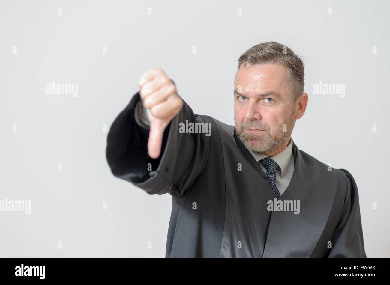 Businessman giving a thumbs down gesture to show he disagrees, a failure or voting down on something, with a stern - Stock Image