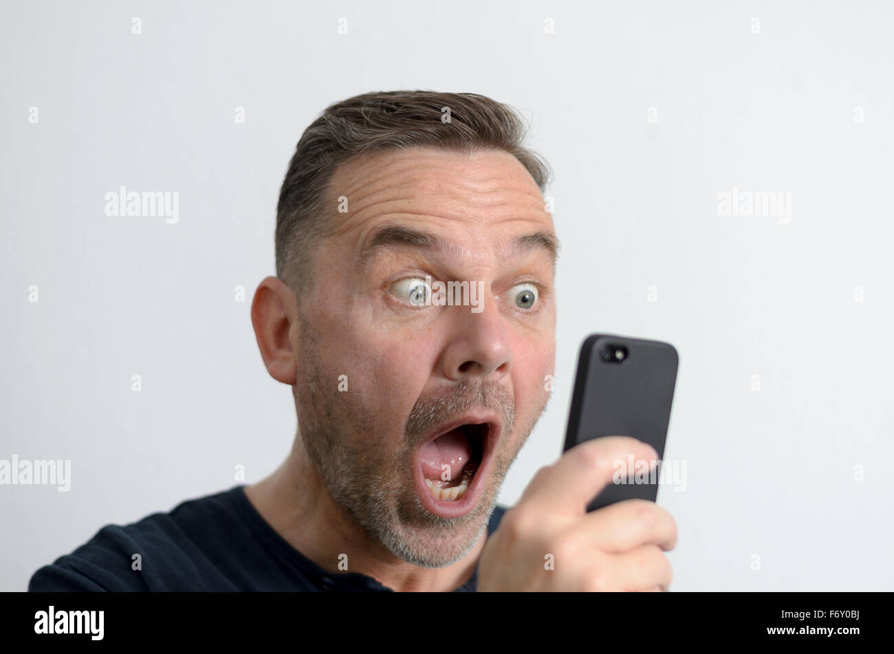 Surprised funny middle-aged man with blue eyes and a shocked facial expression looking at the screen of his mobile - Stock Image